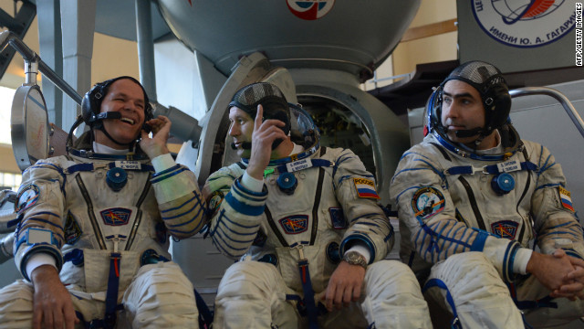 Ford, left, Novitskiy and Tarelkin chat in front of a mockup of the Soyuz rocket before their final preflight practical examination at the Cosmonaut Training Centre in Star City, Russia, on September 21.