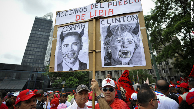 Despite Chavez's recent endorsement of Obama, not everyone approves of the job Washington is doing. Here, protesters hold a poster reading &quot;killers of Libyan people&quot; with portraits of Barack Obama and Hillary Clinton in Caracas, Venezuela, on April 13, 2011.