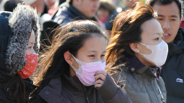 Girls wear face masks to protect against pollution in the streets of Beijing in December 2011.