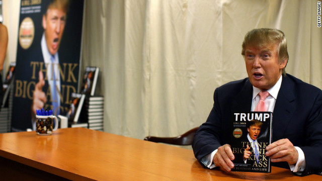 "Trump holds a copy of his new book ""Think Big and Kick Ass in Business and Life"" at a book signing in New York City in 2007."