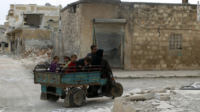 A family drives through Atareb, Syria, which was recently shelled by Syrian government forces, on Wednesday.