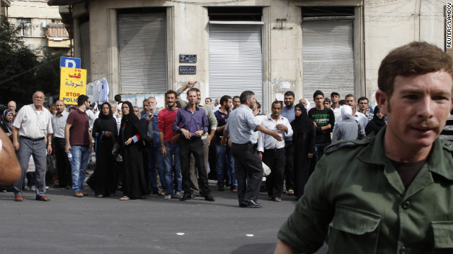 Relatives of Syrian detainees who were arrested for participating in protests against Syrian President Bashar al-Assad's regime wait in front of a police building for detainees to be released in Damascus on Wednesday. The Syrian government said it released a total of 290 prisoners who had not been involved in homicides.
