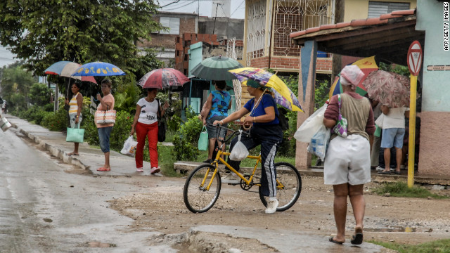 People in Bayamo hold umbrellas as they purchase food Wednesday before the arrival of the hurricane.