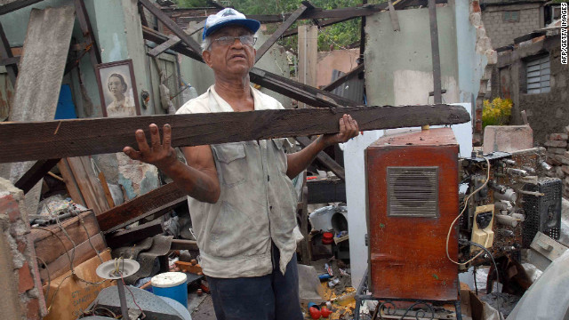 A man clears debris from his house on Thursday. It was demolished by Hurricane Sandy in Santiago de Cuba.