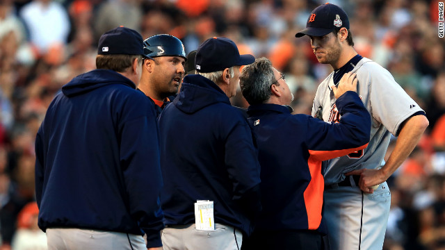 Doug Fister of the Detroit Tigers is checked by Tigers team trainer Kevin Rand after he was hit in the head by a ball off the bat of Gregor Blanco of the San Francisco Giants in the second inning.