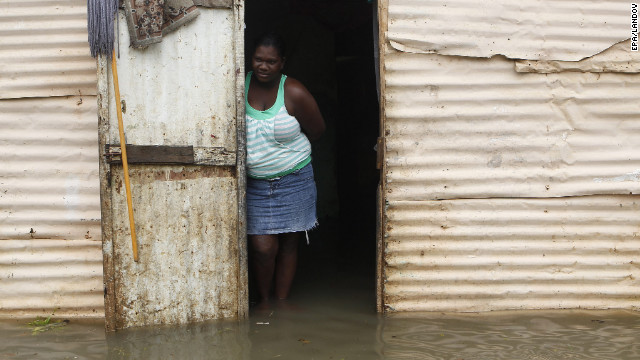 A woman stands at the entrance of her house surrounded by flood water after heavy rains in Santo Domingo, Dominican Republic, on Thursday.