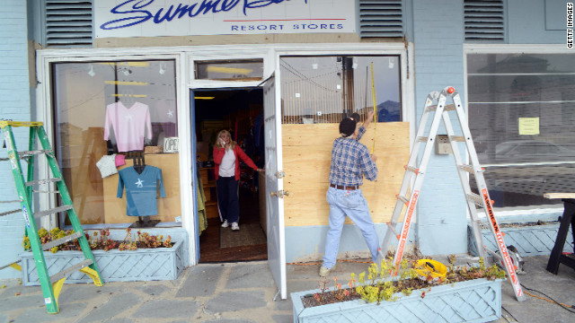 Bob Kaege takes a measurement while boarding up a shop in Cold Spring, New Jersey, as Marie Jadick speaks on the telephone getting an updated weather report in preparation for Hurricane Sandy.