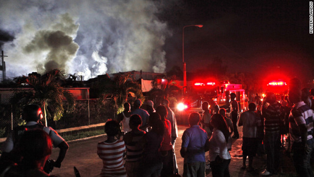 Residents watch firefighters battle a blaze in Kingston, Jamaica, on Friday. The fire, which destroyed the home, was started by a faulty generator that was triggered when Sandy caused a blackout, firefighters said.
