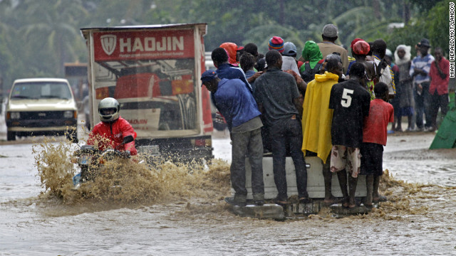 A motorcyclist rides through a flooded street Friday in Petit-Goâve, Haiti, where three overflowing rivers put homes and farms under water.