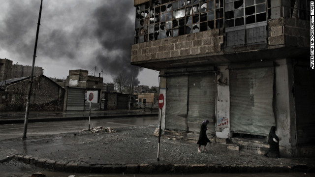 Smoke rises from a gas station following a mortar attack as Syrian women walk by on a rainy day in Aleppo on Thursday, October 25.
