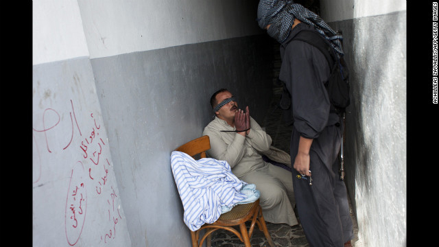 A Syrian rebel interrogates a handcuffed and blindfolded man suspected of being a pro-regime militiaman in Aleppo on October 26, 2012.