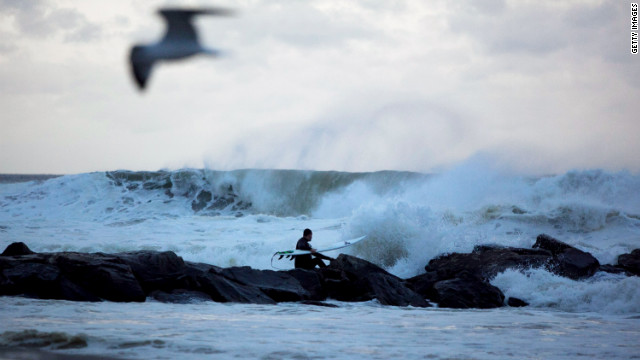 A man surfs at Rockaway Beach in Queens, New York, as Hurricane Sandy approaches on Sunday. Sandy is heading up the East Coast and is forecast to make a possible first landfall near the Delaware coast.