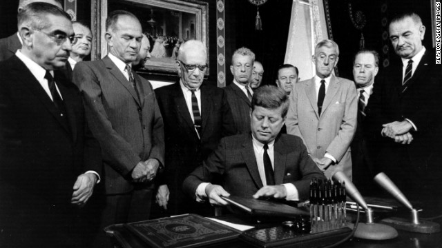 John F. Kennedy signs the nuclear test ban treaty before senators, Vice President Lyndon B. Johnson, right, and Secretary of State Dean Rusk, second from left, foreground. Take a look at what other presidents have done to secure their legacy.