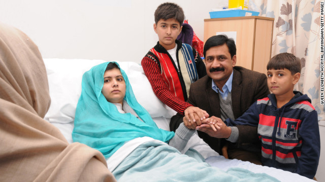 Malala sits up in her hospital bed with her father, Ziauddin, and her two younger brothers, Atal Khan, right, and Khushal Khan on Friday, October 26, at the Queen Elizabeth Hospital Birmingham in Birmingham, England.