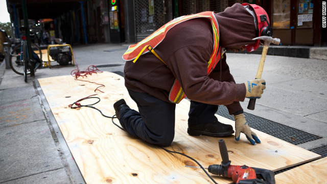 A construction worker covers air vents Sunday to try to prevent the New York subway system from flooding by Hurricane Sandy. New York Gov. Andrew Cuomo announced a shutdown and suspension of all subway, bus and commuter rail service in response to the storm.