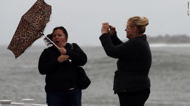 Lisa Cellucci holds her umbrella as it is blown backward by Hurricane Sandy's winds as her friend Kim Vo watches on Sunday in Cape May.
