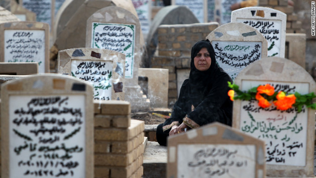 An Iraqi woman sits next to the grave of a relative on Friday at the al-Ghazali cemetery in Baghdad.