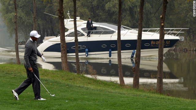 Woods tries to maintain focus as a luxury boat passes by, with the clubhouse car park also boasting a collection of Rolls-Royces, Ferraris, Aston Martins and Maseratis. 