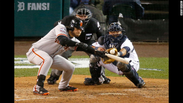 Brandon Crawford of the Giants hits a sacrifice bunt against Phil Coke of the Tigers in the tenth inning.