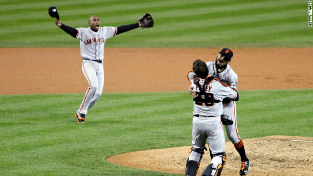 Joaquin Arias of the Giants runs to teammate Sergio Romo as he hugs Buster Posey after striking out Miguel Cabrera of the Tigers in the tenth inning.