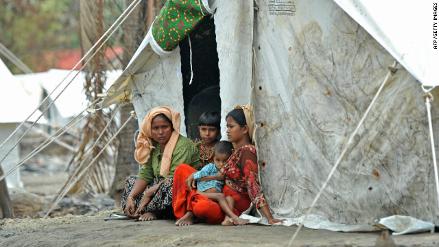 A Muslim Rohingya family sits outside a tent on Sunday. The U.N. says the displaced are in urgent need of assistance.