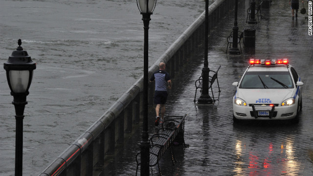 A jogger runs along East River Drive near the Queensboro Bridge in New York City as a police car closed the area down on Monday.