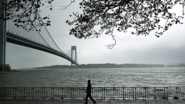 A man walks near the Verrazano Bridge in Brooklyn as Hurricane Sandy moves in.