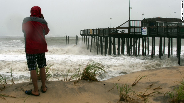 A man watches as the tidal surge pounds a pier in Ocean City, Maryland, on Monday.