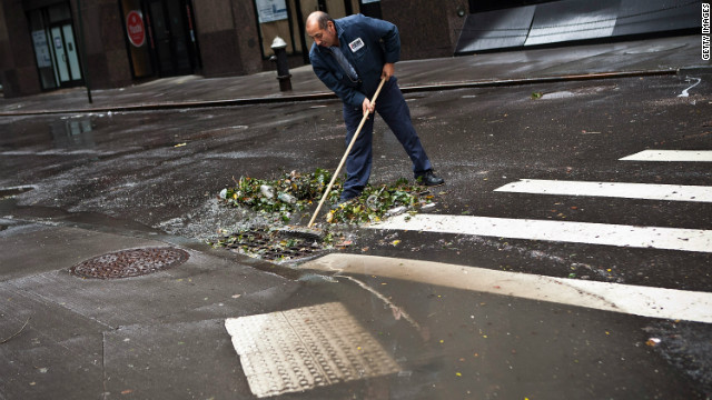 Ramiro Arcos clears debris from a storm drain in the Financial District of New York after Sandy swept through the city. 
