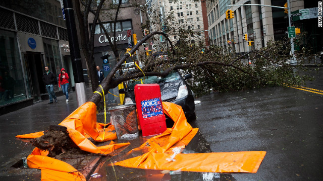 A car sits crushed by a tree in the Financial District on Tuesday. <strong><a href='http://www.cnn.com/2012/10/29/us/gallery/ny-braces-sandy/index.html'>Photos: New York braces for Sandy</a></strong><strong>.</strong>