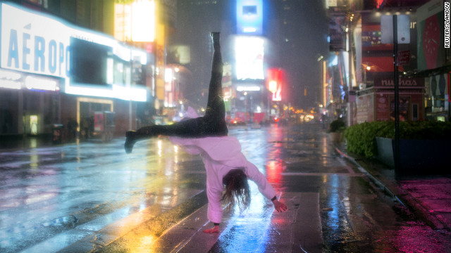 A visitor does a cartwheel in the rain in New York's Times Square on Monday, October 29.