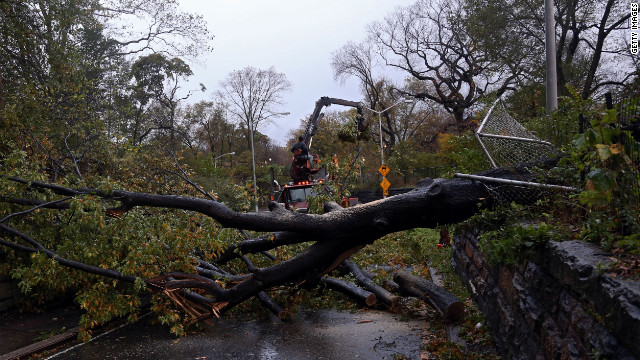 Workers clear a tree blocking East 96th Street in Central Park in New York on Tuesday. View more photos of the recovery efforts in New York.