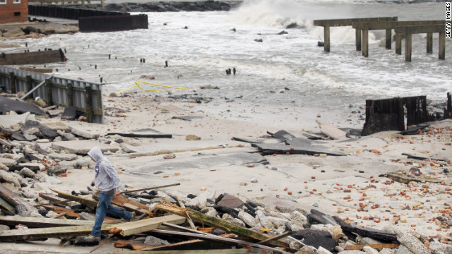  A man walks through the debris of a 2,000-foot section of Atlantic City, New Jersey's &quot;uptown&quot; boardwalk on Tuesday. It was destroyed by flooding from Sandy.