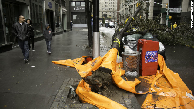 Passers-by look at a car that was crushed by a tree near New York's financial district on Tuesday.