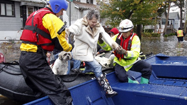 Emergency personnel help a resident of Little Ferry, New Jersey, onto a boat after rescuing her from floodwater on Tuesday.