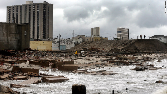 People stand on a mound of construction dirt on Tuesday to view a section of the uptown boardwalk in Atlantic City, New Jersey, that was destroyed by flooding.