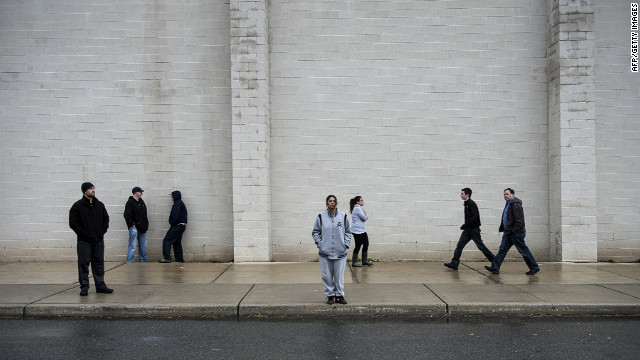 People wait outside a shelter at the Bergen County Technical Schools Teterboro Campus on Tuesday in Hasbrouck Heights, New Jersey. 