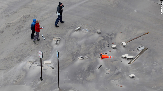 Residents walk along a street covered in beach sand after floodwaters from Superstorm Sandy retreated Tuesday in Long Beach.
