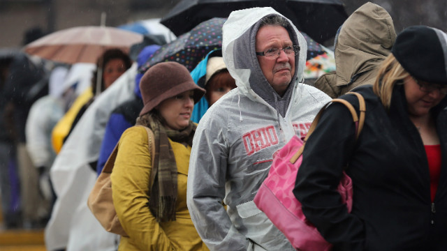 People line up in the rain for a campaign rally with Clinton and Biden on Monday in Youngstown, Ohio.