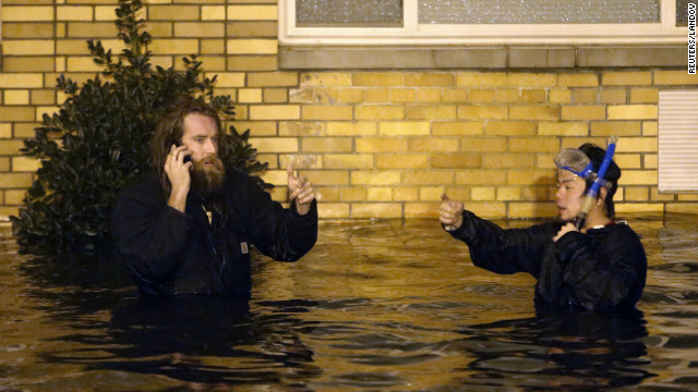 Two men wade through the flooded streets of Brooklyn on Monday as Sandy made landfall.