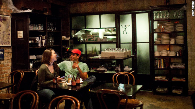 People drink at a bar in New York's East Village during the stormy weather on Monday.