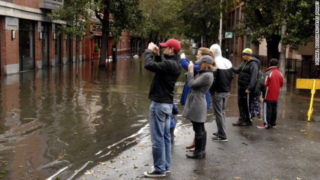 People take pictures of a flooded street Tuesday in Hoboken.