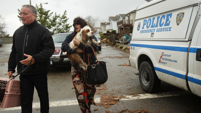 Evacuees leave after Hurricane Sandy caused major destruction in the Queens borough Breezy Point neighborhood in New York City.