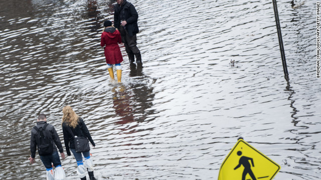 People walk down a flooded street on Wednesday, October 31, in Hoboken, New Jersey. 