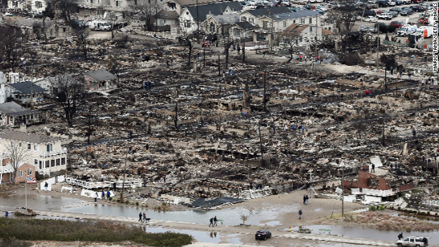 People walk near the remains of burned homes in the Breezy Point neighborhood of Queens, New York, on Wednesday.