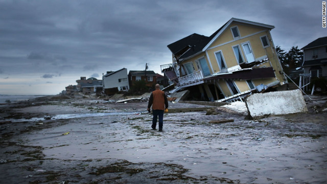 A man surveys damage on Wednesday, October 31, in the Rockaway neighborhood of Queens, New York, where the historic boardwalk was washed away during Superstorm Sandy. 