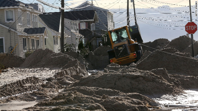 Earth movers push sand off the road that was washed in from Hurricane Sandy on October 31, 2012 in Long Beach Island, New Jersey. 