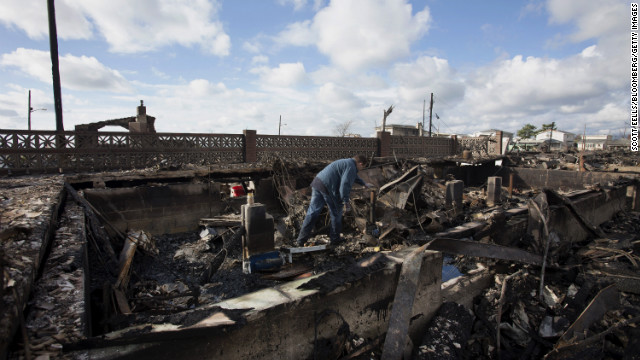 A resident looks through the remnants of his home in the Breezy Point neighborhood of Queens, New York.
