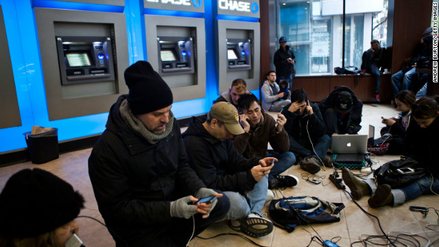 New Yorkers crowd into a Chase Bank ATM kiosk to charge phones and laptops at 40th Street and Third Avenue. 'This is the modern campfire,' one man said.