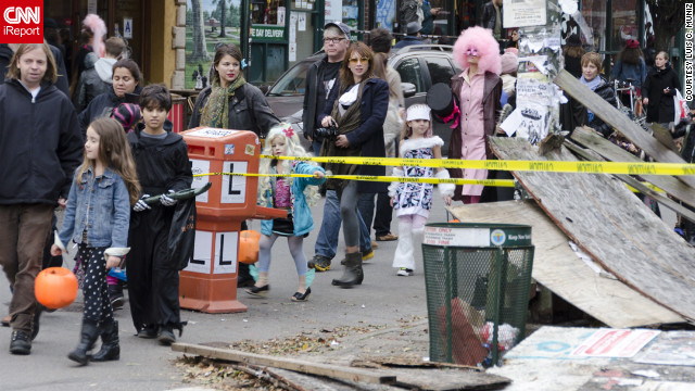 <a href='http://ireport.cnn.com/docs/DOC-869953'>Luis C. Muniz</a> snapped this photo of trick-or-treaters in Brooklyn making their way amid damage brought on by Superstorm Sandy.